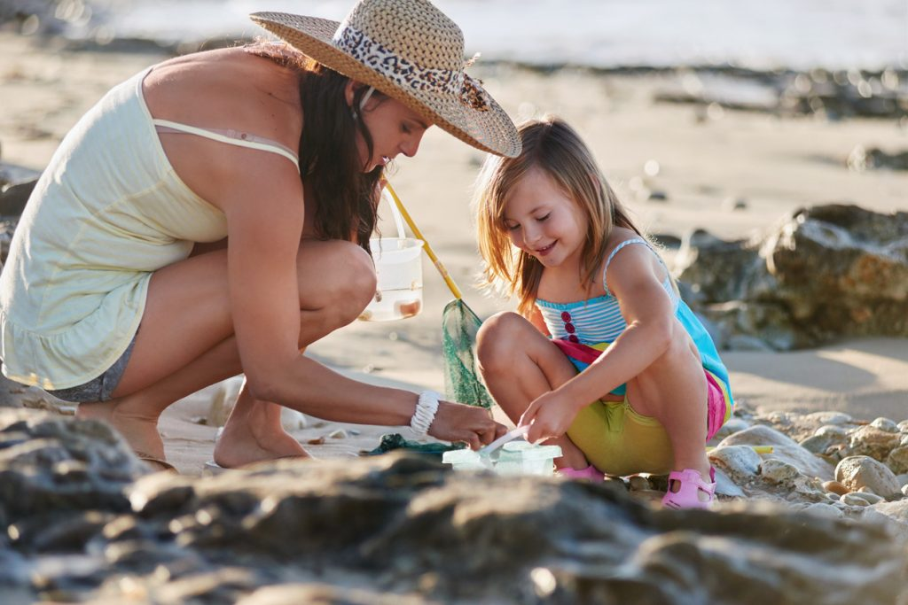 woman and daughter looking in rockpool